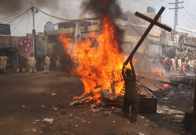 A demonstrator burns a cross during a protest in the Badami Bagh area of Lahore March 9, 2013. An enraged mob torched dozens of houses located in a Christian-dominated neighbourhood of Lahore on Saturday, local media reported. REUTERS/Adrees Hassain